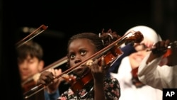 FILE: Migrant Miria, 8 from Angola, resident of the Karatepe municipality camp for refugees in the northeastern Greek island of Lesbos, that have been taught how to play the violin and sing, performs during a concert in Mytilene, Lesbos, Greece, Thursday, Dec. 15, 2016. (AP Photo/Lefteris Pitarakis)