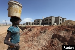 FILE - A woman walks past a Chinese construction site in Lubango, Angola, March 5, 2014.