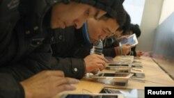 Para pelanggan mencoba iPad di sebuah toko di Shanghai. (Foto: Dok)