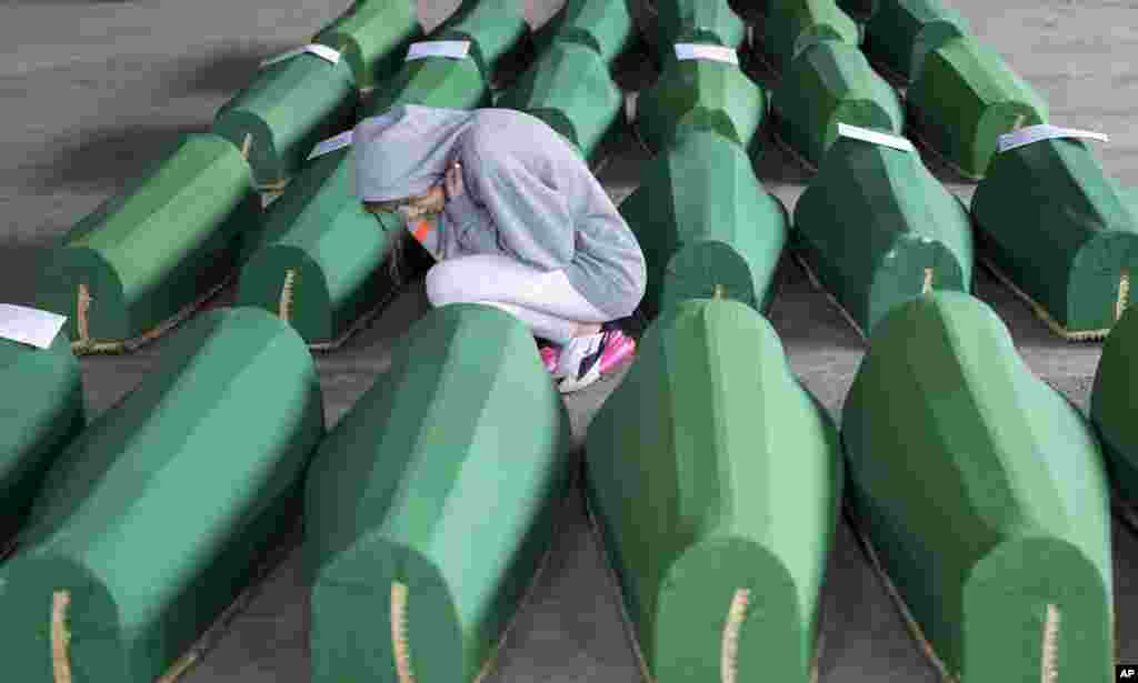 A girl inspects coffins prepared for burial, in Potocari near Srebrenica, Bosnia. The remains of 33 victims of Srebrenica massacre will be buried on July 11, 2019, 24 years after Serb troops overran the eastern Bosnian Muslim enclave of Srebrenica and executed some 8,000 Muslim men and boys.