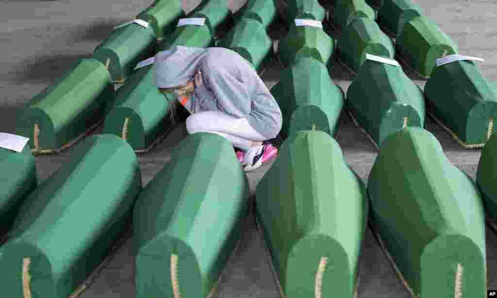 ស្រ្តីម្នាក់ពិនិត្យមើលម្ឈូសដែលត្រូវបានរៀបចំដើម្បីបញ្ចុះនៅក្នុងទីក្រុង Srebrenica ប្រទេសបុស្នី។ ជនរងគ្រោះ៣៣នាក់ដែលបានស្លាប់កាលពីថ្ងៃទី១១ ខែកក្កដា ឆ្នាំ២០១៩។