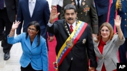 FILE - Venezuela's President Nicolas Maduro, then Constituent National Assembly President Delcy Rodriguez, left, and first lady Cilia Flores, wave as they arrive to the National Assembly, in Caracas, Venezuela, May 24, 2018. The Trump administration slapped financial sanctions Tuesday, Sept. 25, 2018, on four members of Maduro's inner circle, including his wife, and Rodriguez who is now the nation's vice president, on allegations of corruption.