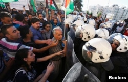 Protesters argue with Palestinian riot police during a protest against security coordination between Palestinian authority and Israel, in the West Bank city of Ramallah, June 23, 2014.