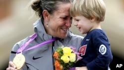La medallista de oro Kristian Armstrong, de Estados Unidos, celebra con su hijo Lucas, la presea dorada del ciclismo contrareloj.