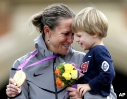 FILE - Gold medalist Kristin Armstrong of the United States celebrates with her son, Lucas, after the women's individual time trial event at the 2012 Summer Olympics in London, Aug. 1, 2012.
