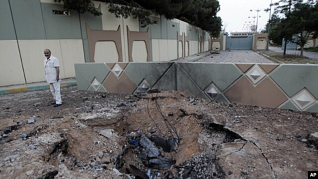 In this photo taken on a government organized tour a Libyan official stands next to a crater left after an airstrike at Moammar Gadhafi's Bab al-Aziziya compound in Tripoli, Libya, June 1, 2011.