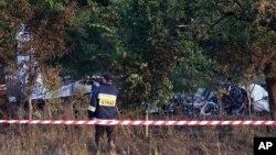 Seorang petugas pemadam kebakaran memeriksa lokasi jatuhnya pesawat terbang dekat desa Topolow di Polandia (5/7).