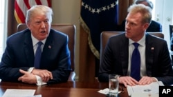 FILE - In this April 9, 2018, photo, Deputy Secretary of Defense Patrick Shanahan, right, listen as President Donald Trump speaks during a cabinet meeting at the White House, in Washington.