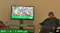 In this image from a TV broadcast by Libyan television, Libyan leader Moammar Gadhafi sits next to a TV monitor showing a strapline at the bottom in English, reading 'The Leader's speech to the Libyan people 07 06 2011
