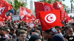 Protestors gather during an anti-extremism march, in Tunis, Sunday, March 29, 2015. Tens of thousands of Tunisians from across the political spectrum marched through the capital Sunday to denounce extremist violence after a deadly museum attack on foreign