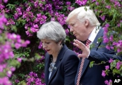 U.S. President Donald Trump, right, talks with British Prime Minister Theresa May in Taormina, Italy, May 26, 2017.