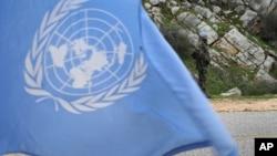 Một binh sĩ gìn giữ hòa bình đứng phía sau lá cờ Liên Hiệp Quốc.