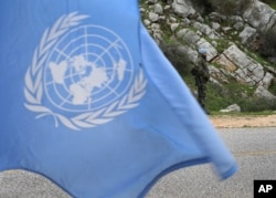 FILE - A United Nations peacekeeper is seen standing behind a U.N. flag.