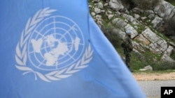FILE - A United Nations peacekeeper is seen standing on patrol behind a U.N. flag.