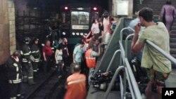 Люди покидают остановленный поезд. Снимок камеры мобильного телефона. Москва, 5 июня 2013г.