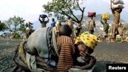یک زن رواندایی با کودکش بر پشت در راه پیمایی به سوی کمپ پناهندگان ازپادرآمده است. ۲۸ ژوییه ۱۹۹۴