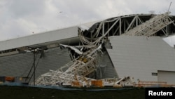 """Para pekerja bangunan berdiri di dekat sebuah derek yang rubuh di station Sao Paulo (27/11). Stadion yang dikenal sebagai """"Itaquerao"""" ini akan menjadi tuan rumah Piala Dunia (World Cup) 2014."""