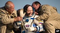 اولگ آرتميف، مهندس پرواز اکتشافی ۴۰، عضو سازمان فضانوردی فدرال روسيه، در حالی که به او کمک میکنند تا از کپسول سويوز، در منطقه پرت افتادهای در قزاقستان، خارج شود، برای استقبال کنندگان دست تکان میدهد. پنجشنبه، ۲۰ شهريور ۱۳۹۳ (۱۱ سپتامبر ۲۰۱۴)