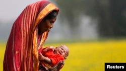 FILE - A woman holds her 22-day-old grandson as she walks on the outskirts of Dhaka, Bangladesh, Jan. 22, 2014.
