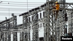 An employee works on electric pylons at a power station in Greater Noida on the outskirts of New Delhi. (file)