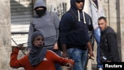 Para pemuda Palestina bersenjatakan batu dan ketapel bentrok dengan pasukan keamanan Israel di kota Hebron, Tepi Barat, Kamis (29/10).