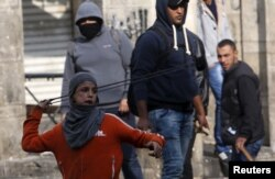 A Palestinian boy uses a sling to hurl stones towards Israeli troops during clashes in the West Bank city of Hebron, Oct. 29, 2015.