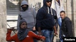 Un jeune palestinien lance une pierre contre les forces de sécurité israéliennes au cours des affrontements à Hébron, 29 octobre 2015. REUTERS/Mussa Qawasma