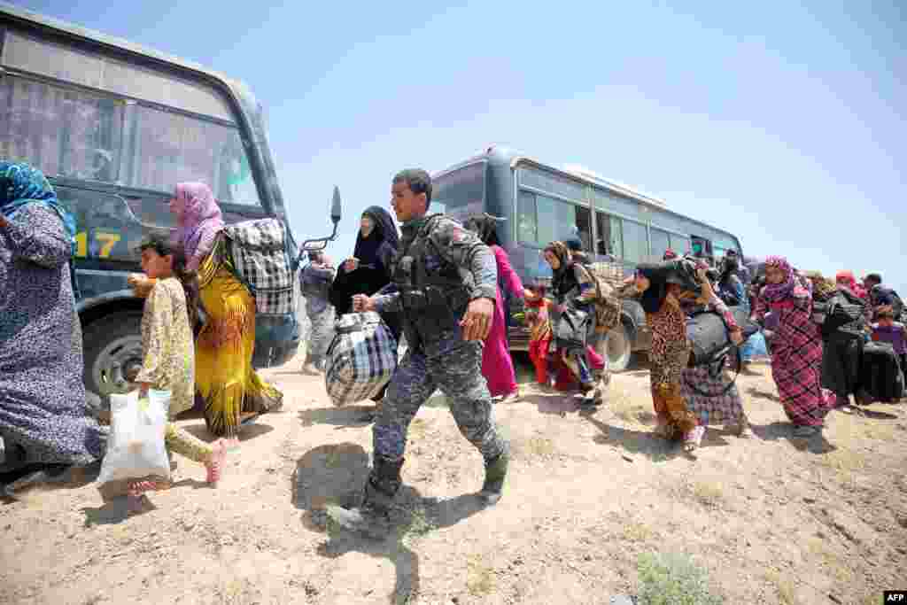 Iraqi forces help families near al-Sejar village in Anbar province after fleeing Fallujah on May 27, 2016, during a major operation to retake Fallujah from Islamic State.