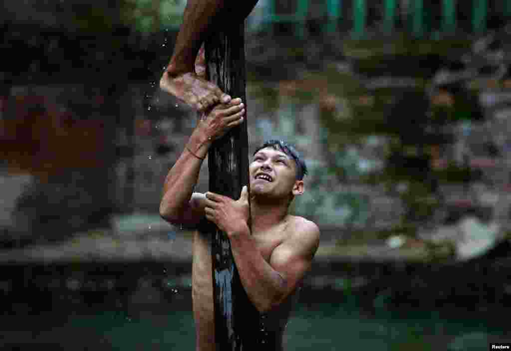 A devotee helps his friend to climb the wooden pole during the Deopokhari festival in Khokana, Nepal, Aug. 9, 2017.