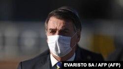 资料照:巴西总统贾尔·博尔索纳罗(Jair Bolsonaro)在巴西利亚阿尔沃拉达宫举行部长级会议前举行升旗仪式时戴着口罩。(2020年5月12日)