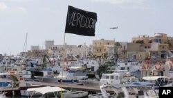 """Sebuah bendera hitam bertuliskan """"Vergogna"""" (malu) dikibarkan di pelabuhan pulau Lampedusa, Italia (4/10). Italia berkabung pasca tenggelamnya kapal yang mengangkut pencari suaka dari Eritrea dan Somalia di dekalt pulau Lampedusa, Kamis (3/10). Sekitar 300 orang dinyatakan tewas dalam insiden tersebut."""