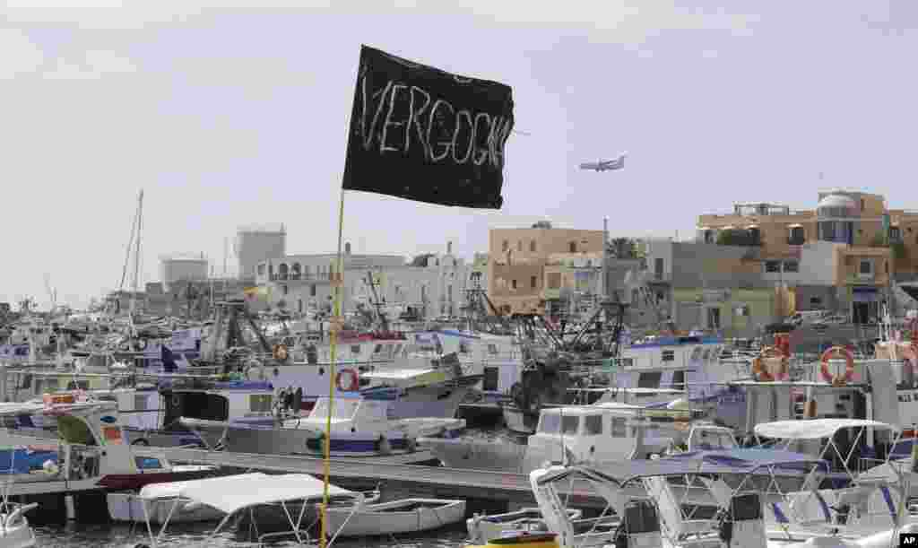 "A black flag with writing reading in Italian ""Vergogna"" (shame) waves in the harbor of the island of Lampedusa, Italy, Oct. 4, 2013."