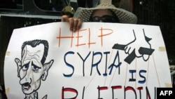 Người biểu tình mang biểu ngữ và tranh biếm họa của Tổng thống Syria Bashar Assad trong cuộc biểu tình chống chính phủ Syria gần đại sứ quán Syria tại Cairo