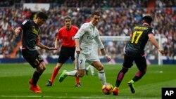 Cristiano Ronaldo du Real Madrid, au centre, perce avec le ballon entre Gerard Moreno de l'Espanyol, à gauche, et le co-équipier de ce dernier, Hernan Perez, lors d'un match de la La Liga espagnole au stade Santiago Bernabeu à Madrid, 18 février 2017.