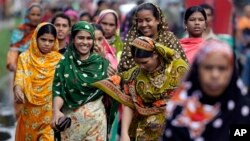 Bangladeshi garment workers arrive for work early morning in Dhaka, Bangladesh, Sept. 12, 2012.