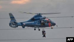A police helicopter lifts an evacuee with a rescue police officer from floodwaters in Joso city in Ibaraki prefecture, north of Tokyo, Sept. 10, 2015.