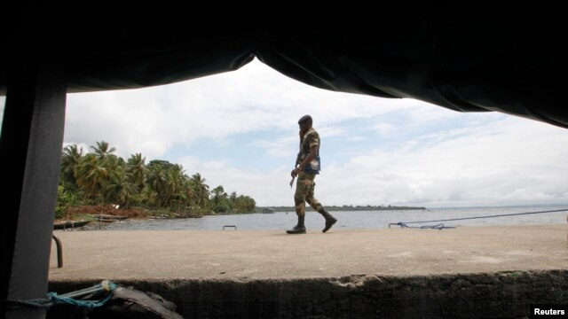 Ivorian soldier patrols town of Adiake, near their border with Ghana, Sept. 24, 2012.