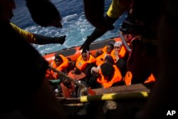 Women and children wait their turn to get on onboard the rescue vessel Golfo Azzurro by members of the Spanish NGO Proactiva Open Arms, after being rescued from a wooden boat sailing out of control in the Mediterranean Sea, about 18 miles north of Sabrath Libya, June 15, 2017.