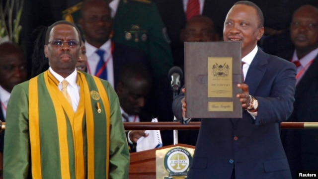 Kenya's President Uhuru Kenyatta displays his certificates of oath from Chief Justice Willy Mutunga during the swearing-in ceremony at Kasarani Stadium in Nairobi, Apr. 9, 2013.
