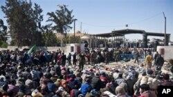 Wakimbizi wakisubiri kuvuka mpaka wa Libya na kuingia Ras Ajdir nchini Tunisia.