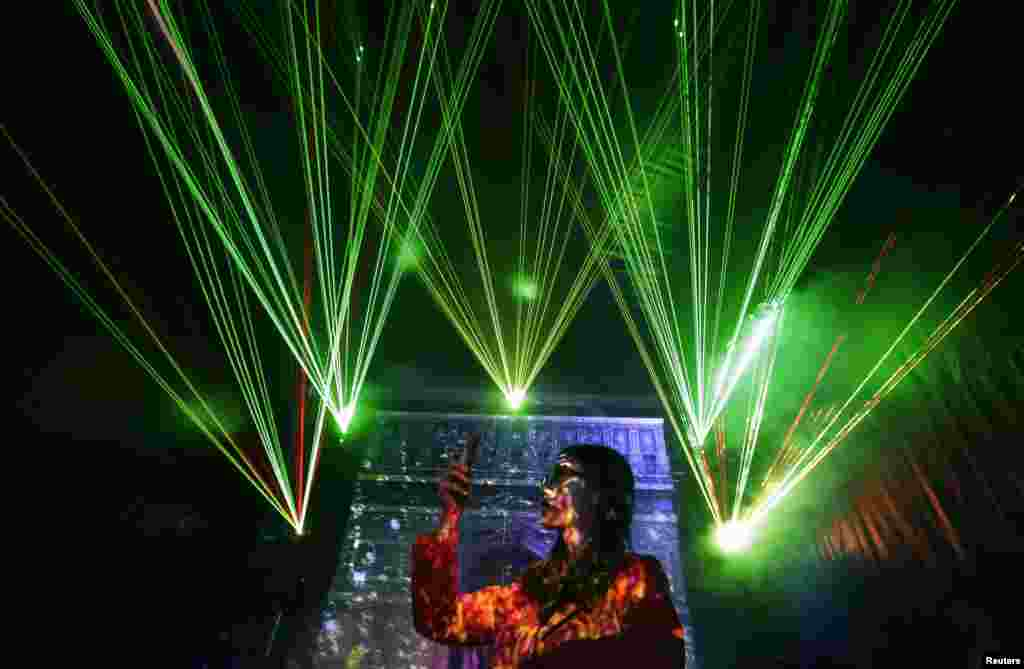 A visitor takes pictures with her mobile phone in front of laser beams and a projected image of the Arc de Triomphe, at the 2013 Optic Valley of China International Optoelectronic Exposition and Forum (OVC EXPO) in Wuhan, Hubei province, China.