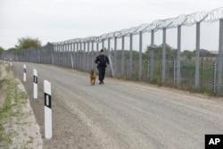 Un policía con un perro patrulla la valla fronteriza en la frontera húngara-serbia cerca de Roszke, a 180 km al sureste de Budapest, Hungría, el 28 de abril de 2017. Hungría ha pedido a la UE que pague la mitad del costo de la cerca construida para evitar el ingreso de inmigrants ilegales.