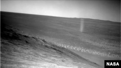 A dust devil is seen swirling across the Martian surface in this photo snapped by the Mars Opportunity rover.