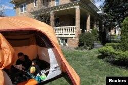 Warga AS, Andrew Kolb, sedang membaca buku dengan anaknya, James, 5, di dalam tenda yang didirikan di halaman rumah, selama masa isolasi di tengah penyebaran virus corona di Washington, U.S., April 2, 2020