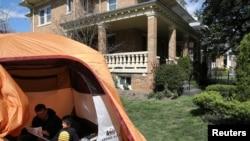 Andrew Kolb fait la lecture à son fils James, 5 ans, de l'intérieur d'une tente qu'ils ont planté dans leur cour pour passer du temps pendant l'isolement social de la famille à cause de COVID-19 à Washington, États-Unis, le 2 avril 2020. (Photo: REUTERS / Leah Millis)