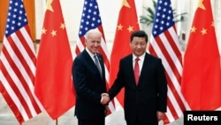 FILE - Chinese President Xi Jinping shakes hands with U.S. Vice President Joe Biden (L) inside the Great Hall of the People in Beijing.