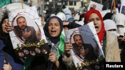 FILE - Protesters from the Islamic Action Front, carry pictures of the deputy overall leader of Jordanian Muslim Brotherhood Zaki Bani Rsheid during a demostration to show their solidarity with Palestinians, in Amman, November 28, 2014.