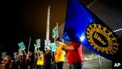 Jeff Elkins, de 37 años, empleado de una fábrica de GM, ondea una bandera del sindicato de trabajadores automotrices( United Auto Workers) al final del turno de medianoche de la Planta de Ensamblaje de Flint, Michigan. Sep.16 de 2019. Foto: Jake May/The Flint Journal via AP.
