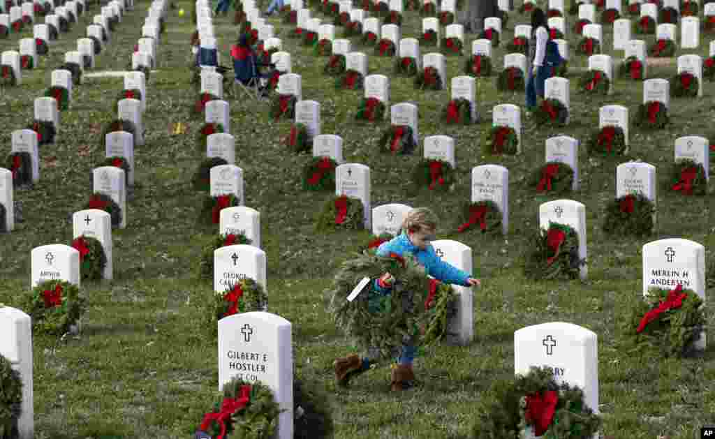 Lane Austin, 6, of Virginia Beach, carries a wreath to grave during Wreaths Across America at Arlington National Cemetery, in Arlington, Virginia, Dec. 12, 2015.