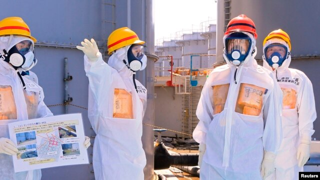 Japan's Prime Minister Shinzo Abe (2nd R), wearing protective suit and mask, is briefed about tanks containing radioactive water by Fukushima Daiichi nuclear power plant chief Akira Ono (2nd L), as they stand near a tank (C, with railings painted red and